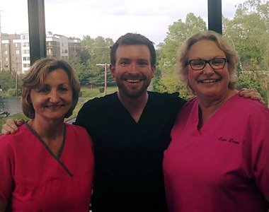 Dentist and two team members smiling together