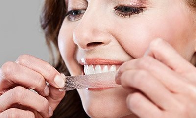 Woman placing teeth whitening strip