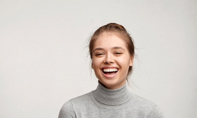 young woman in gray sweater laughing