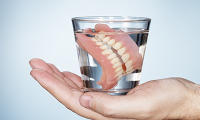 Dentures stored in glass of water