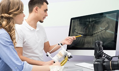 Dental assistant and patient looking at dental x-rays