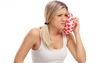 woman holding cold compress to her face