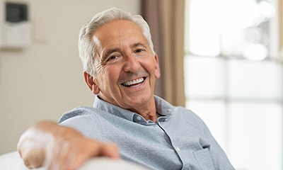 Older man smiling with an implant-retained bridge in Wethersfield