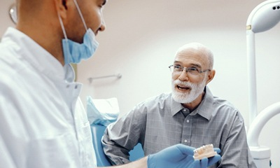 Dentist explaining implant-retained dentures in Wethersfield to male patient