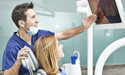 Dentist and patient looking at intraoral photos