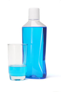 blue mouthwash in bottle and glass