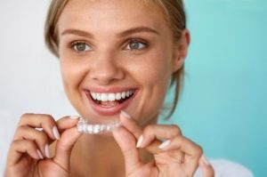 Smiling woman putting a whitening tray in