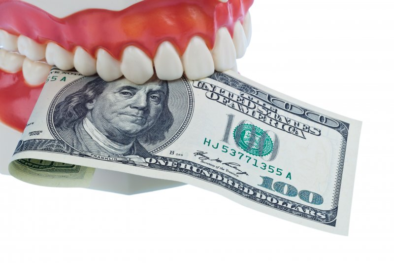 model mouth holding bill in between teeth
